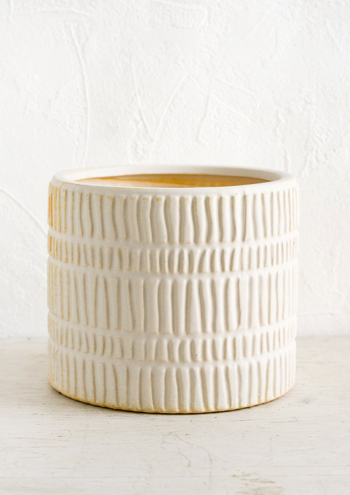 Large: A bisque ceramic planter with rows of raised line texture throughout.