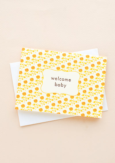 "Greeting card with yellow and orange floral print and ""Welcome baby"" text at center"