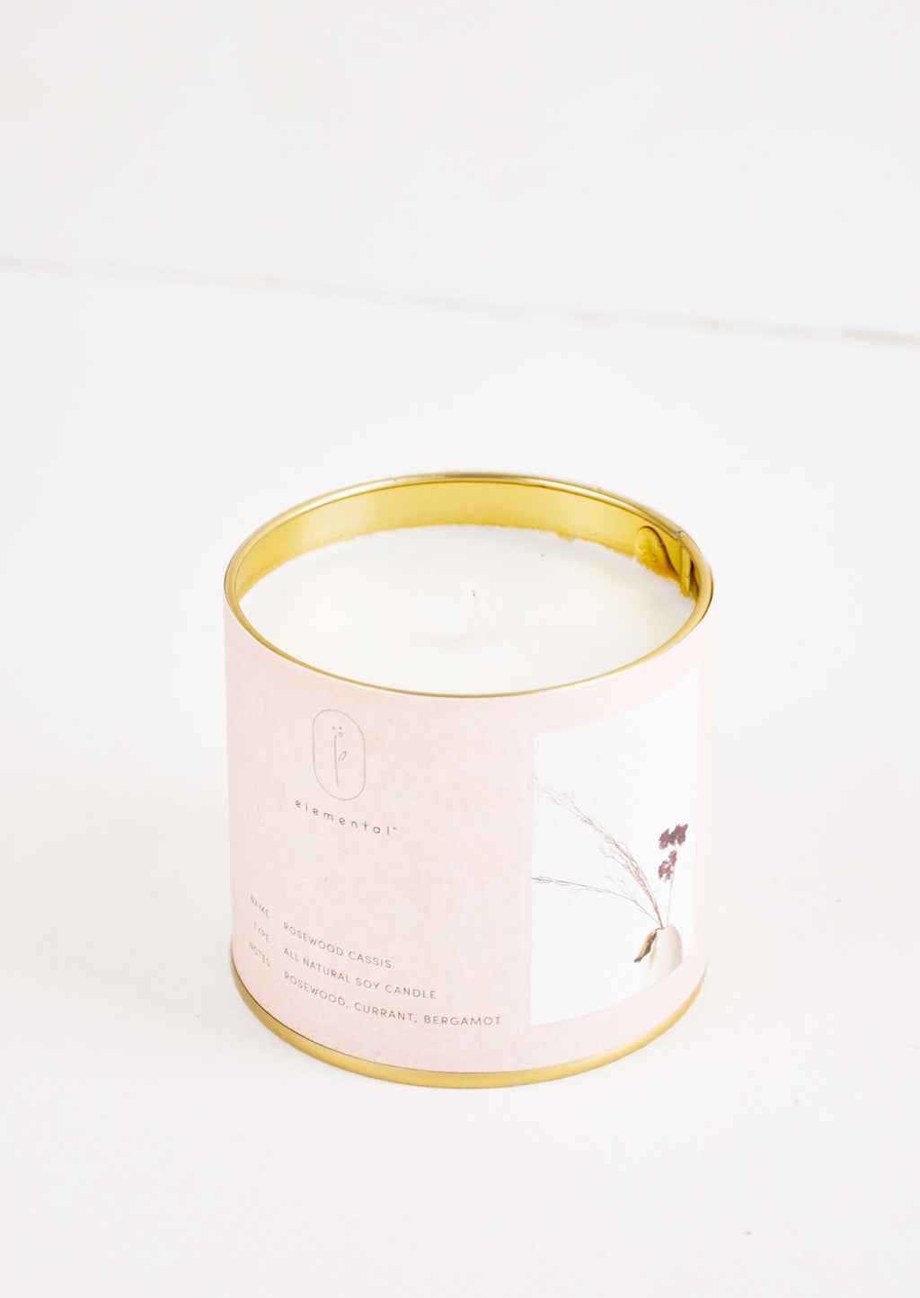 Rosewood Cassis: A candle in a brass tine with a pale pink label featuring a picture of a flower.