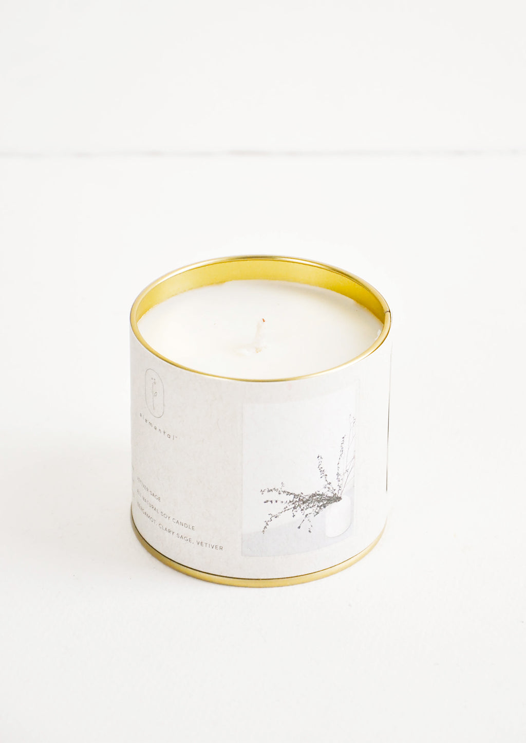 Vetiver Sage: A candle in a brass tin with a gray label featuring a picture of grasses.