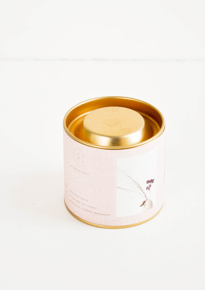 5: A candle in lidded brass tin with a pale pink paper label.