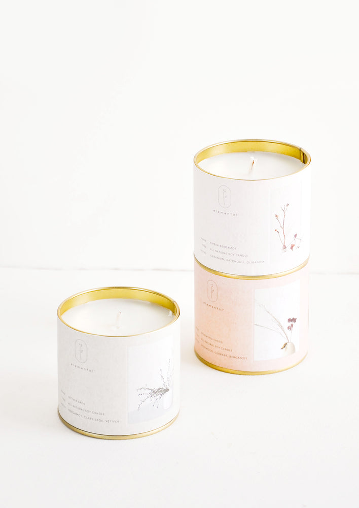 1: Three candles in brass tins with paper labels of gray, beige, and pale pink.