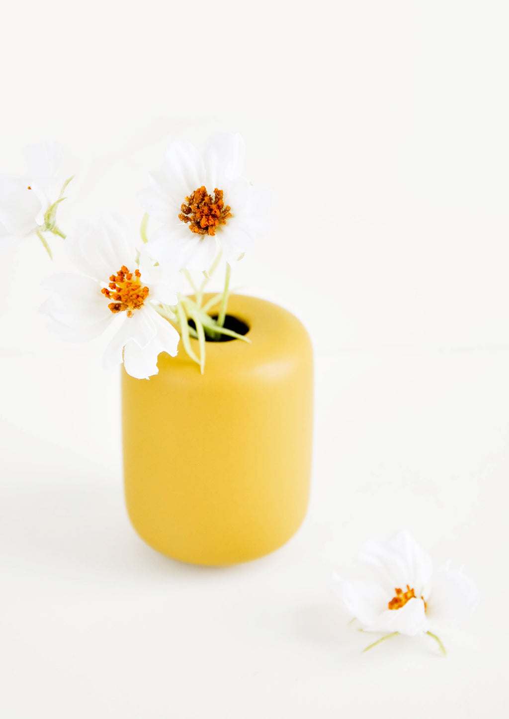 2: Small, tubular shape ceramic bud vase in matte mustard, shown with flowers