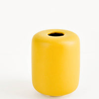 1: Small, tubular shape ceramic bud vase in matte mustard