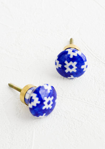 Two ceramic cabinet knobs in white and cobalt blue with tile pattern.