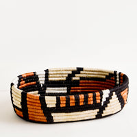 Black Multi: Oval shaped shallow bread basket made from woven natural grass in black and terracotta geometric print