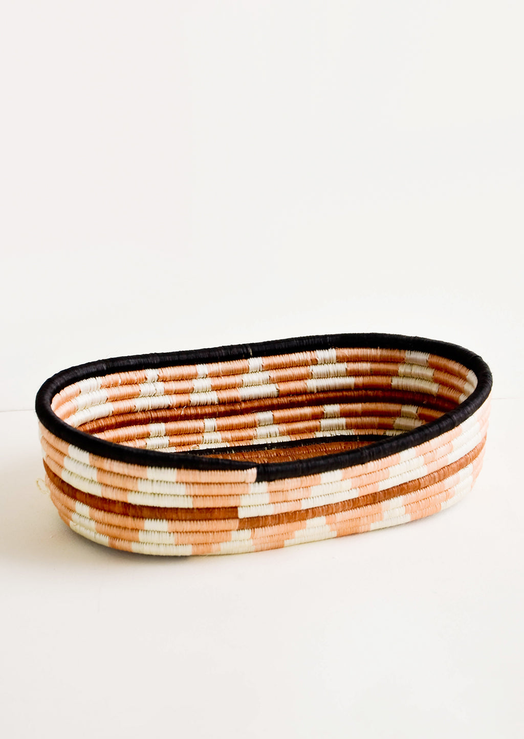 Peach Multi: Oval shaped shallow bread basket made from woven natural grass in peachy geometric pattern