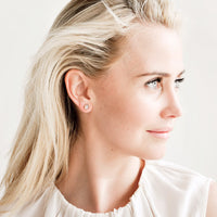 2: Blonde model wearing silky white shirt and gemstone stud earrings.