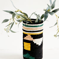 Black Geo Multi: Tall vases made of woven natural grass in colorful geometric pattern, with eucalyptus leaves inside