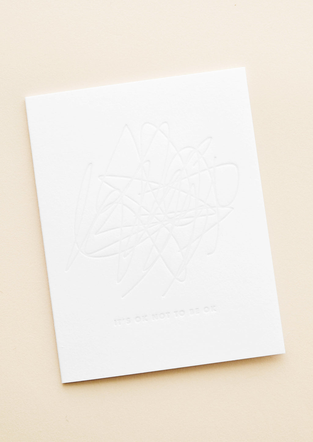 "1: A simple white card with an imprint of a hectic scribbled blob and the words ""it's okay to not be okay."""