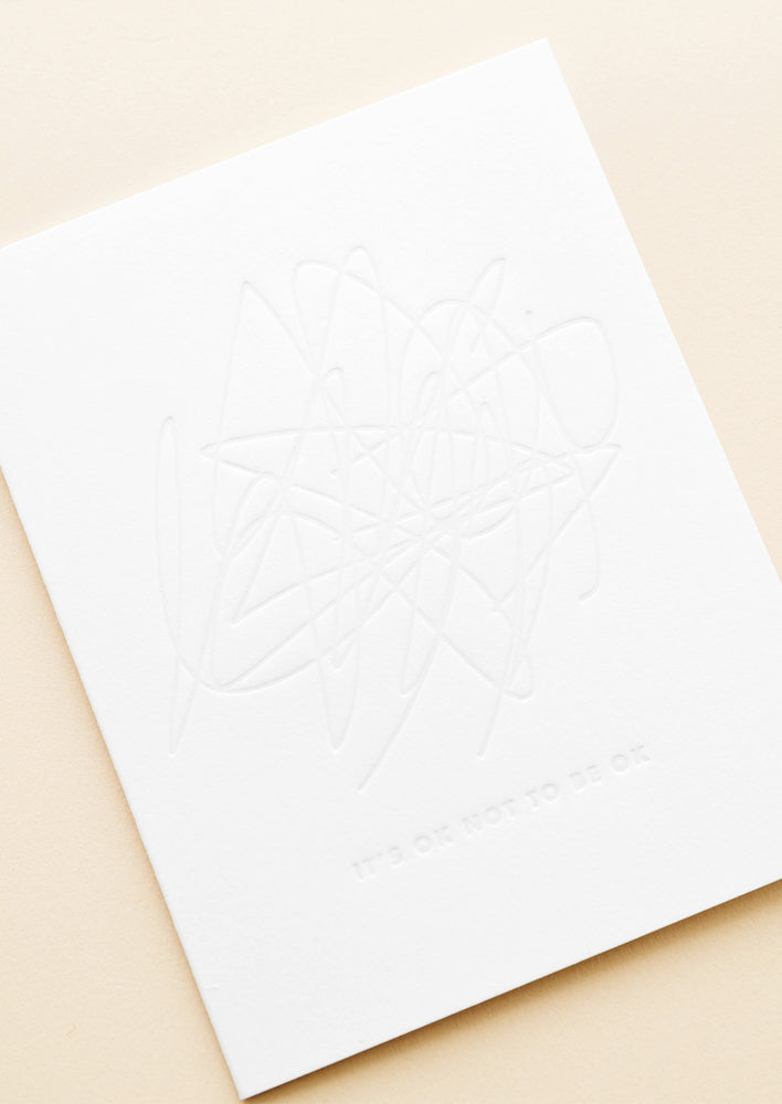 "2: A simple white card with an imprint of a hectic scribbled blob and the words ""it's okay to not be okay."""