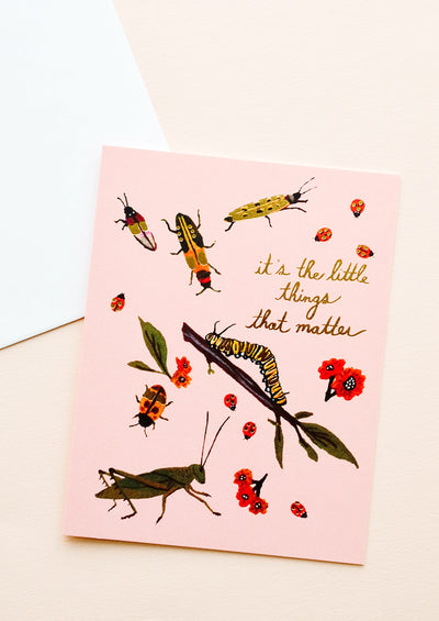 "Pink greeting card with ladybugs, insects and flowers and gold text reading ""It's the little things that matter"""