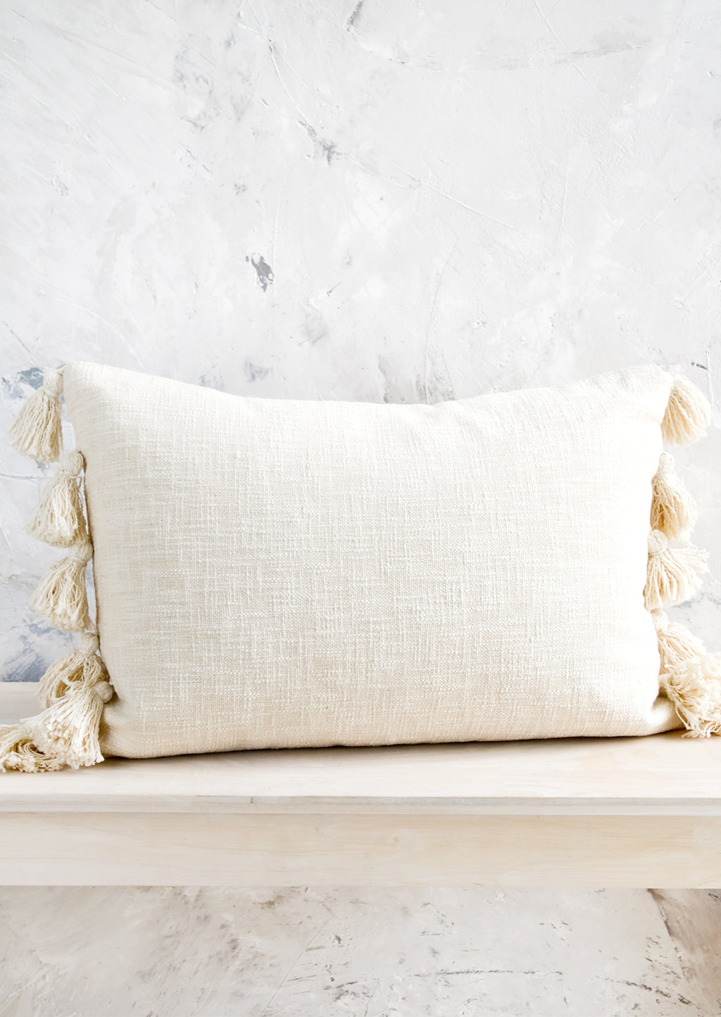 1: Lumbar throw pillow in textured, cream colored cotton with large decorative tassels at sides.
