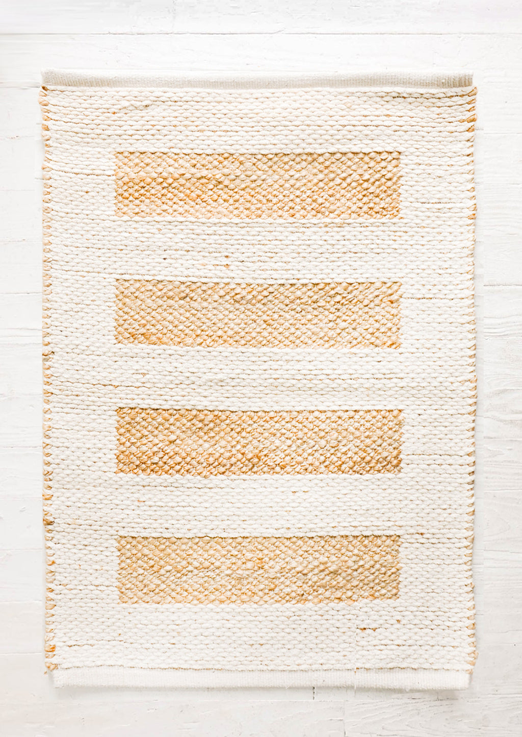 1: Rug in ivory cotton with contrasting bar stripe pattern in natural jute.