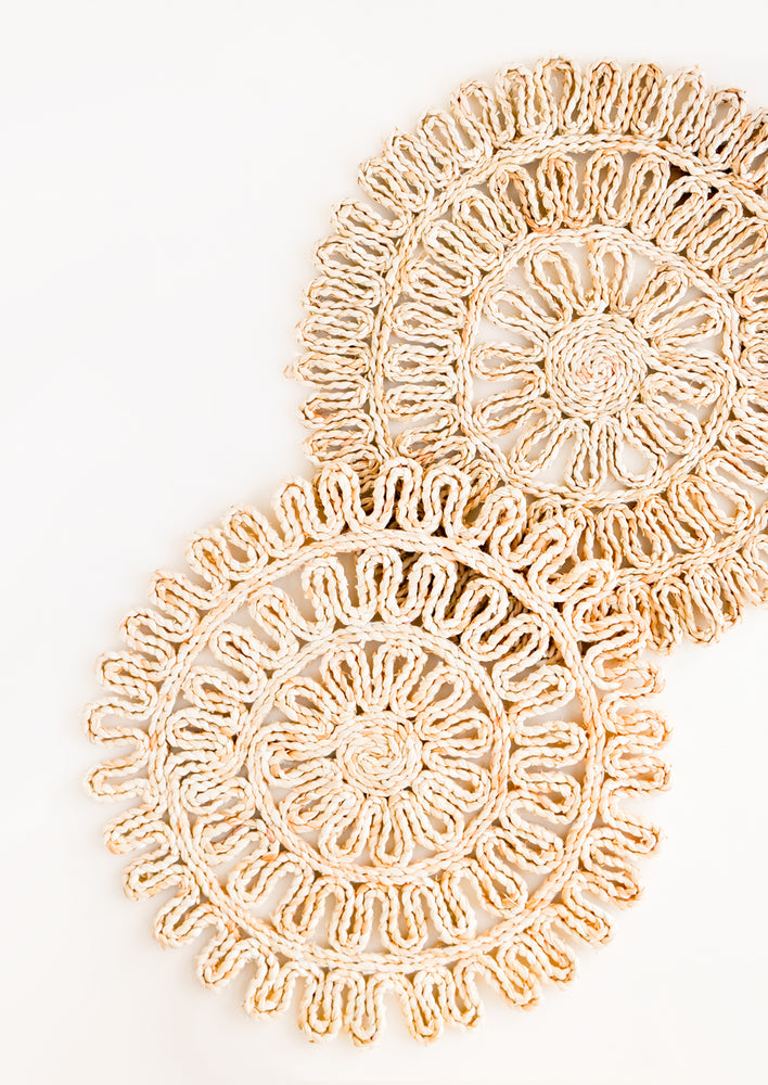Set of two round placemats in natural straw in a decorative woven pattern