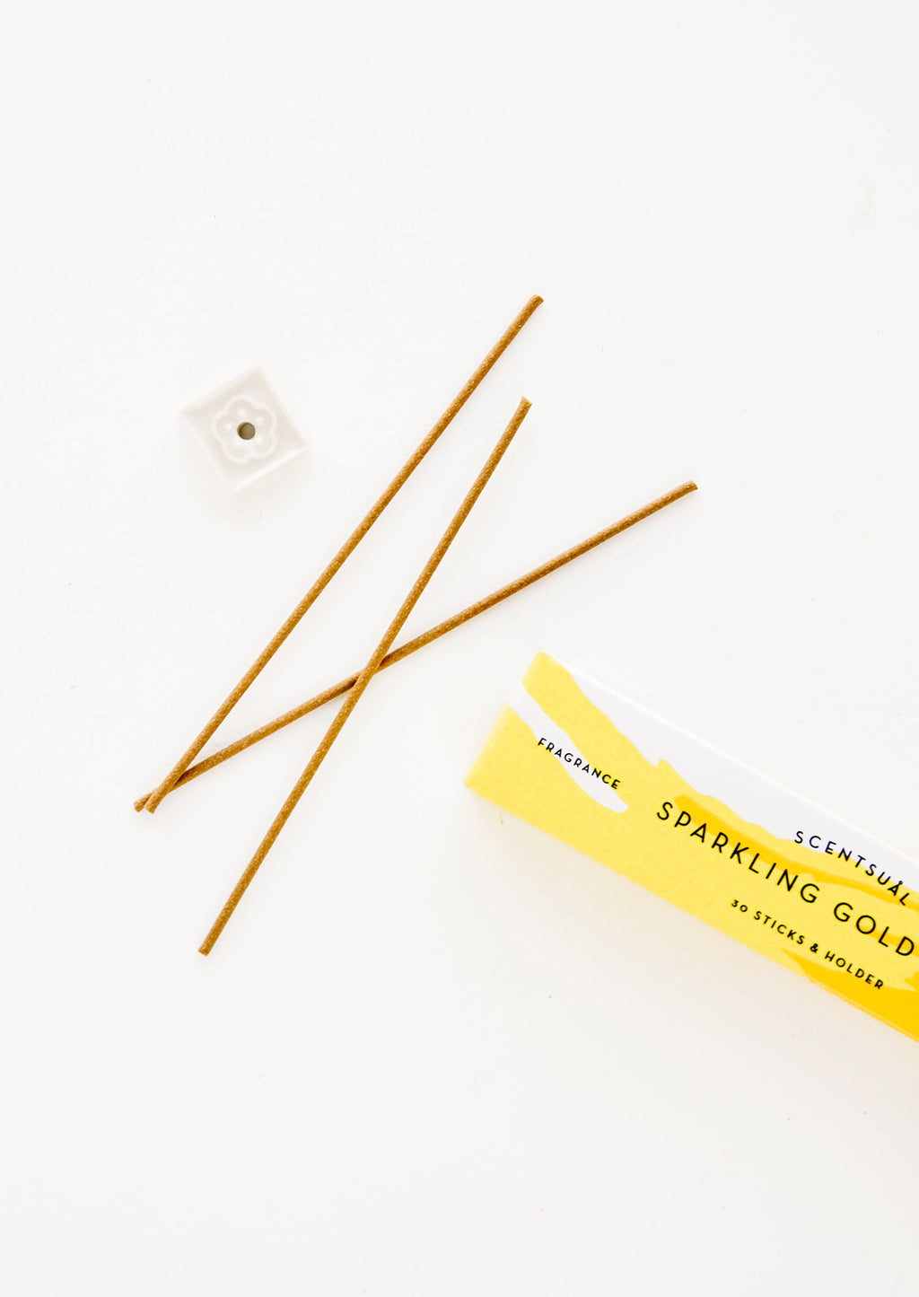 Gold Yuzu: Three thin incense sticks laid out next to a small square holder and yellow cardboard box.