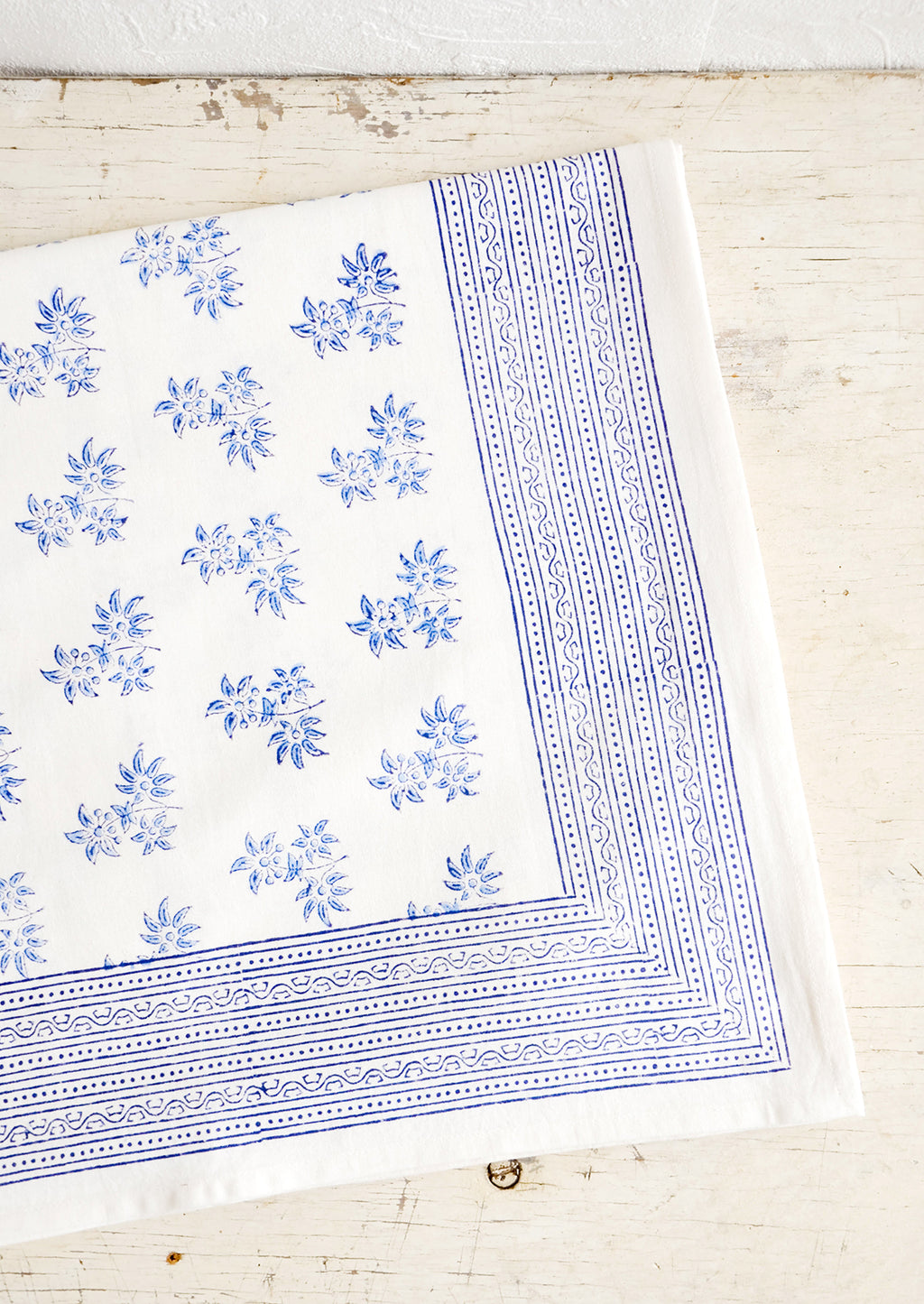 1: White cotton tablecloth with blue floral print, folded on an antique table.