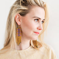 2: Model shot showing woman wearing earrings and a peach top.