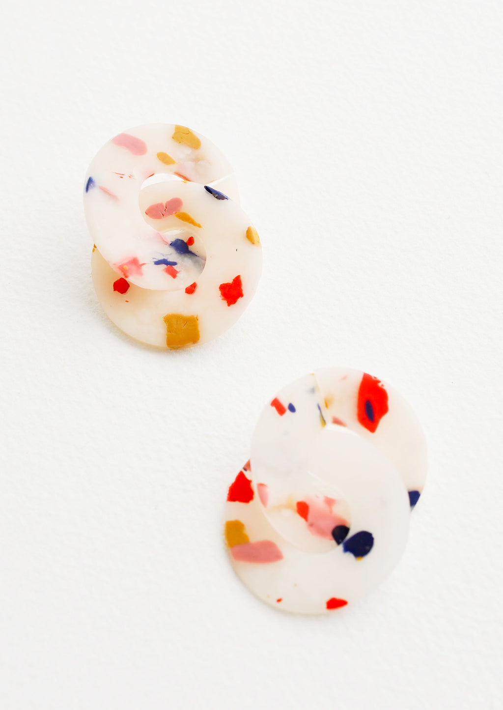 1: Post back earrings of intertwined pink, blue, and yellow speckled translucent clay discs.