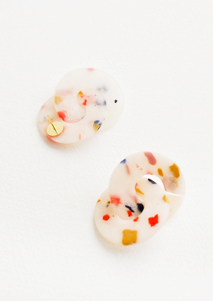 3: Post back earrings of intertwined pink, blue, and yellow speckled translucent clay discs.