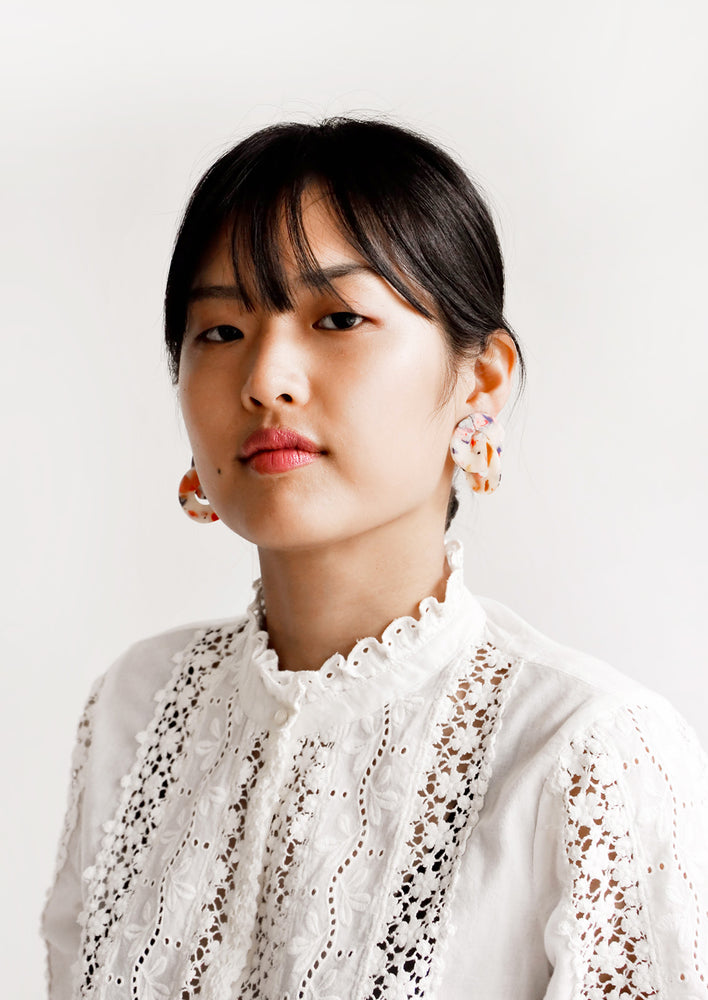 2: Model wears speckled interlocking earrings and white blouse.