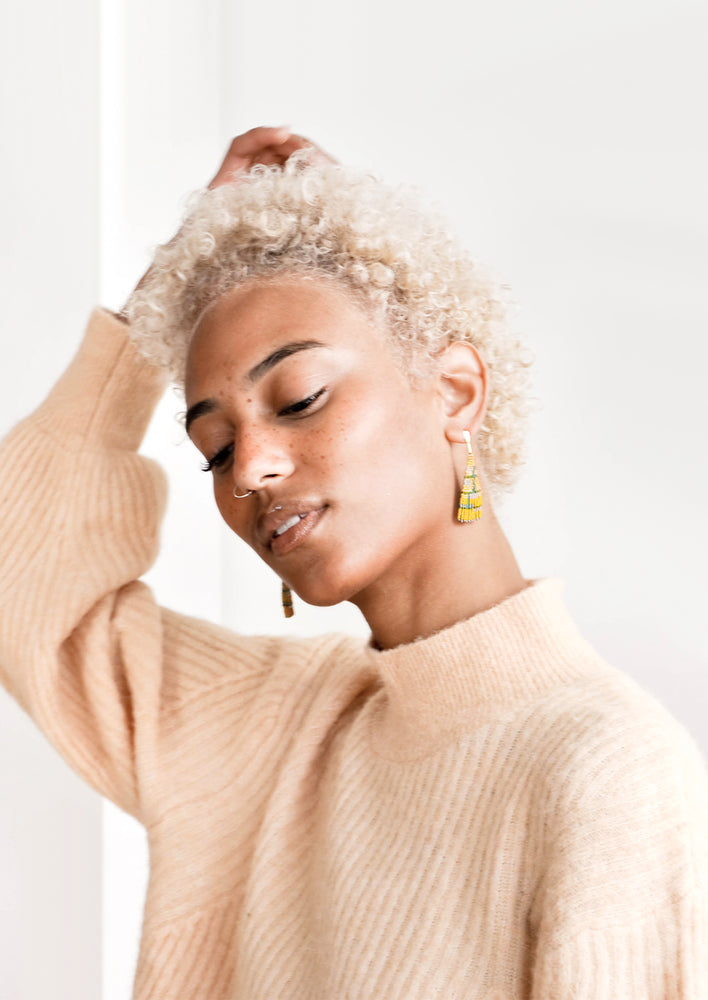 2: Model wears yellow triangle shaped beaded earrings and peach sweater.
