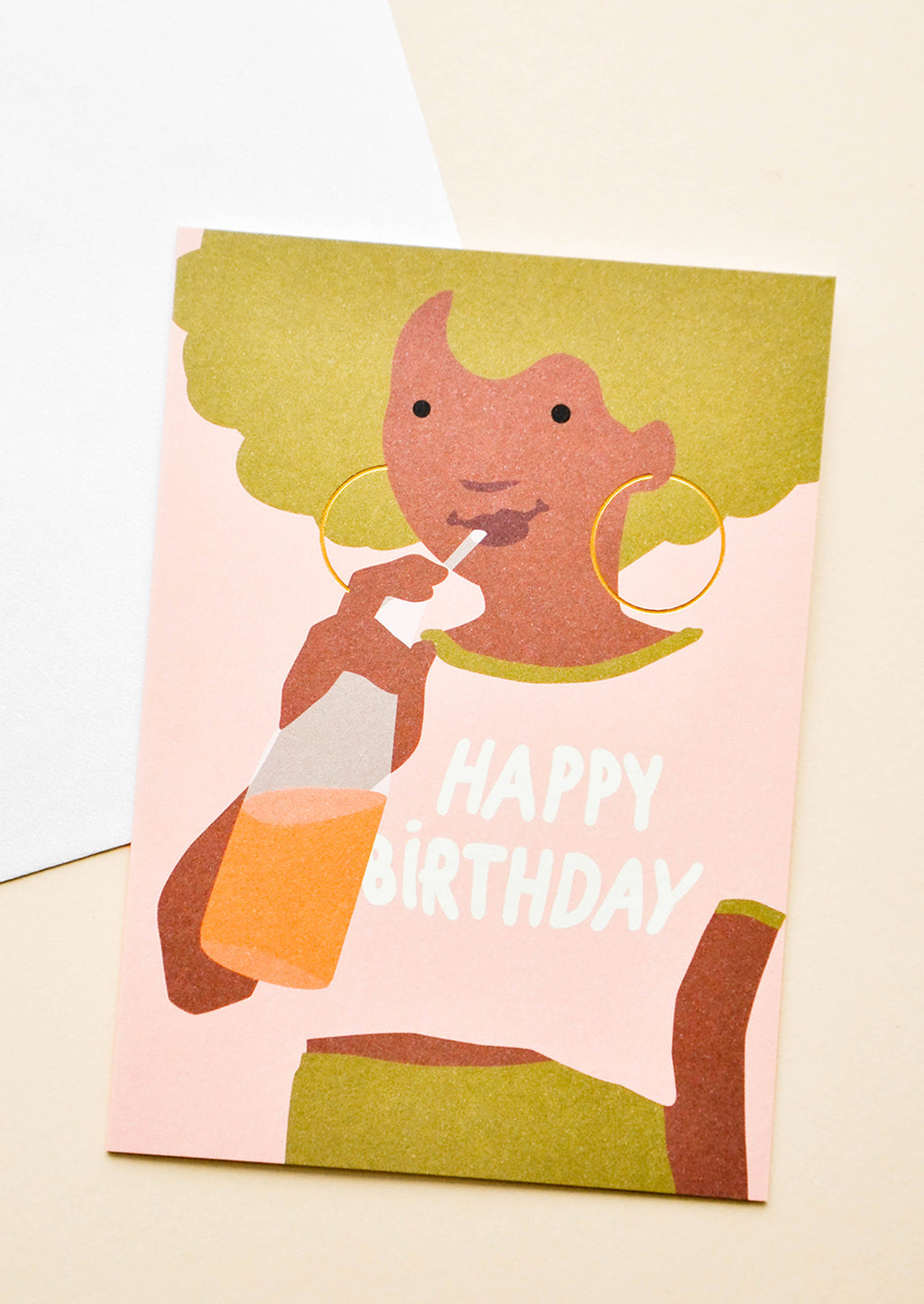 "1: Greeting card with illustration of girl with green hair, drinking orange soda with ""Happy Birthday"" written on her pink t-shirt. Shown with white envelope."