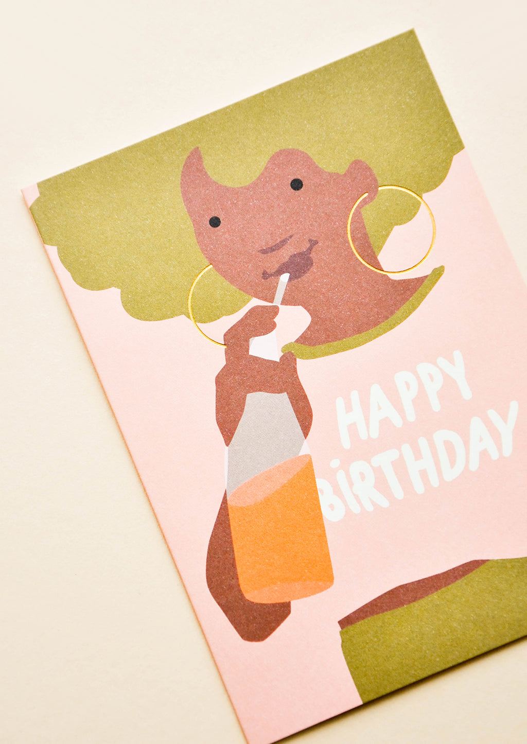 "2: Greeting card with illustration of girl with green hair, drinking orange soda with ""Happy Birthday"" written on her pink t-shirt"