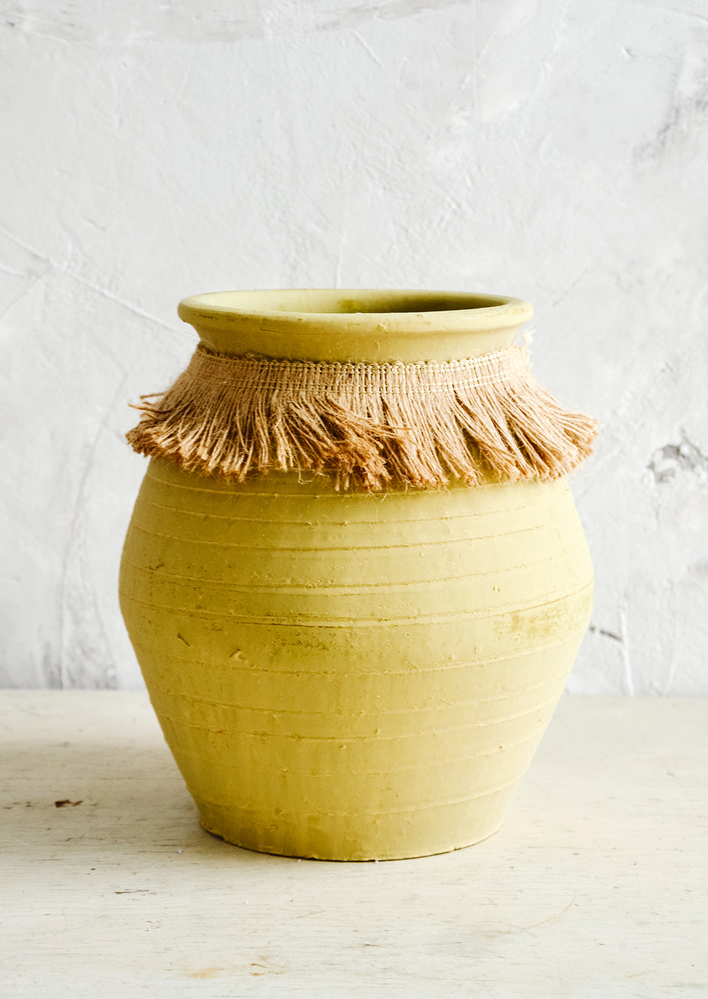 Large: Tall, ochre colored clay vase with fringed jute trim around opening