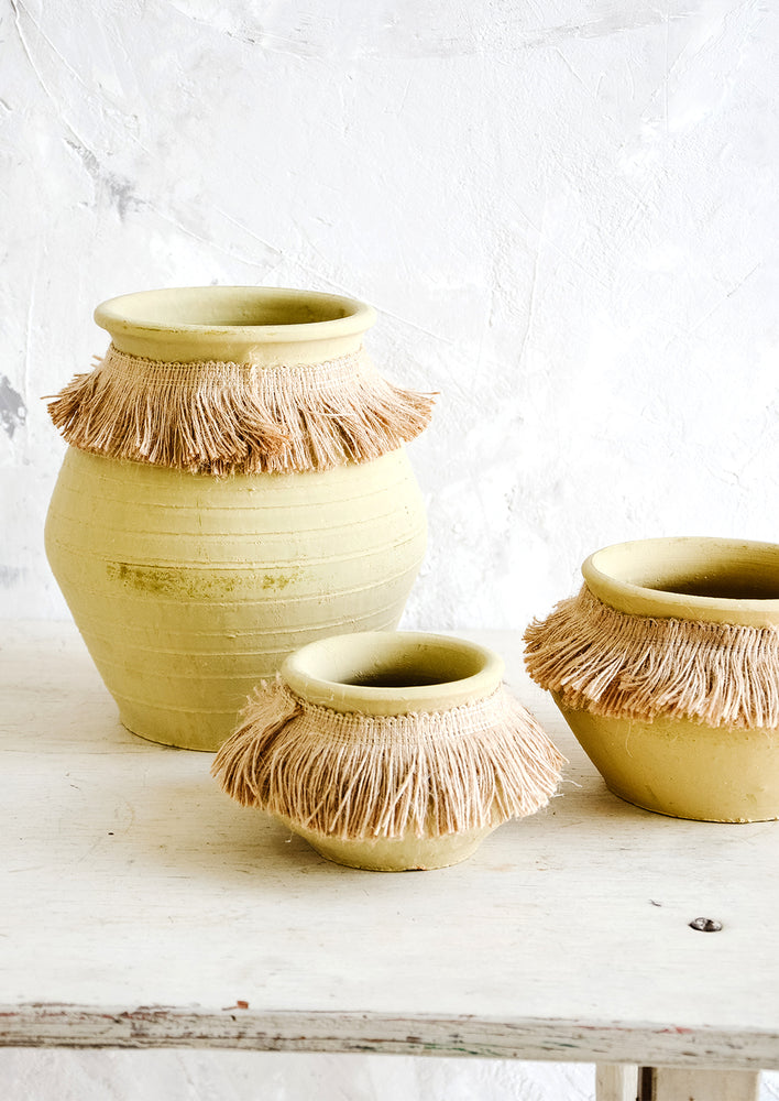Medium: Three ochre clay vases in incremental sizes with fringed jute trim around opening