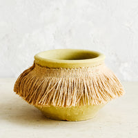 Small: Short, ochre colored clay vase with fringed jute trim around opening