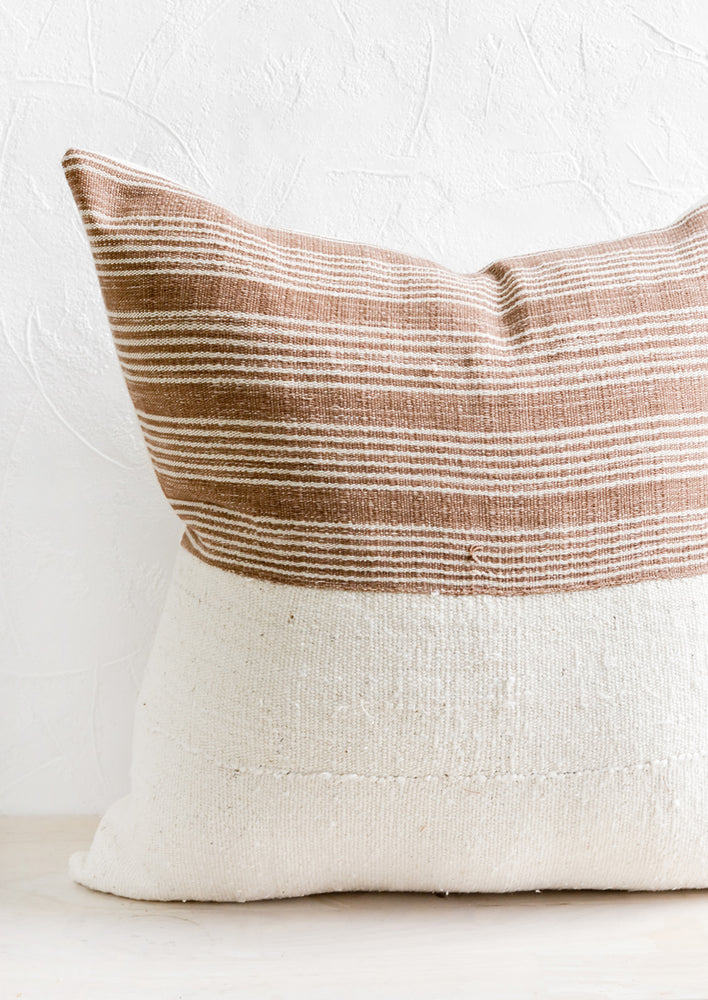 A throw pillow with top half in brown & ivory striped fabric and bottom half in natural mudcloth.