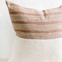 1: A throw pillow with top half in brown & ivory striped fabric and bottom half in natural mudcloth.