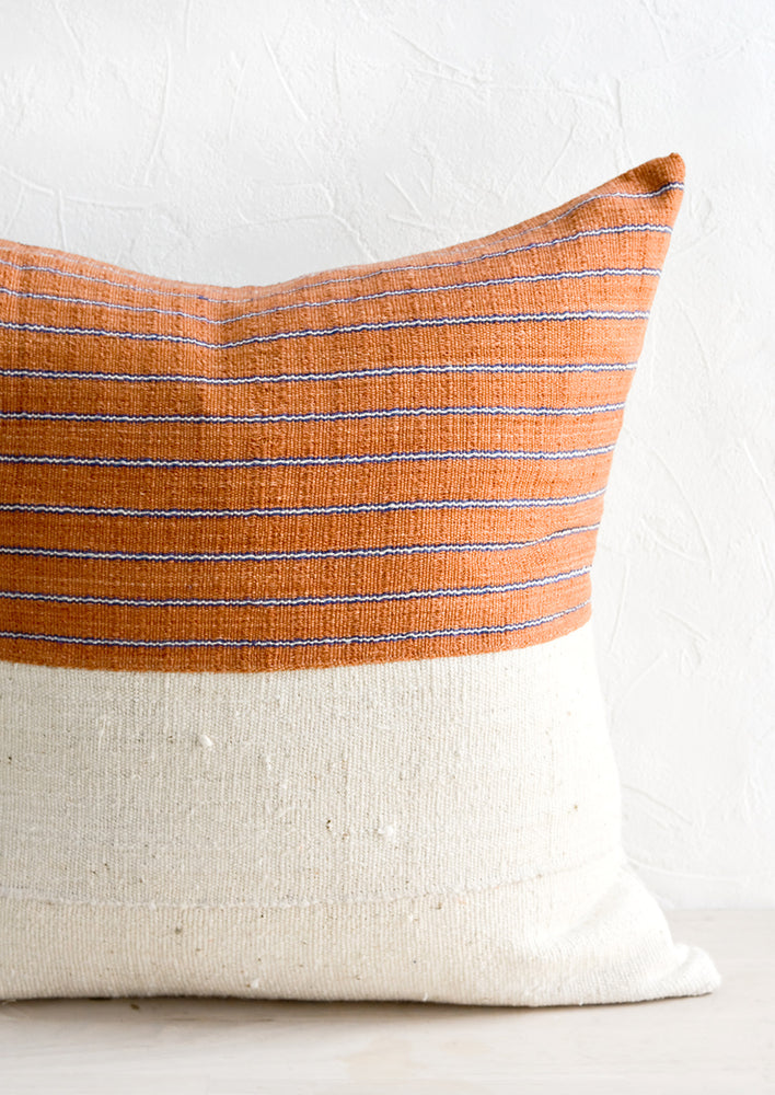 1: A throw pillow with top half in rust & indigo striped fabric and bottom half in natural mudcloth.