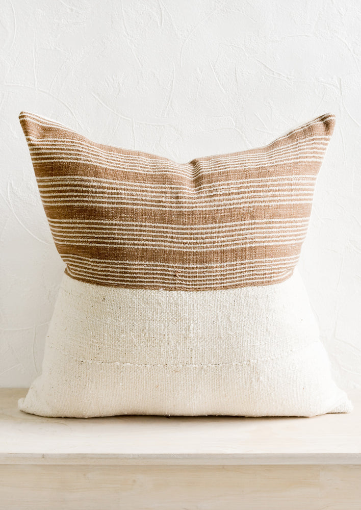 2: A throw pillow with top half in brown & ivory striped fabric and bottom half in natural mudcloth.