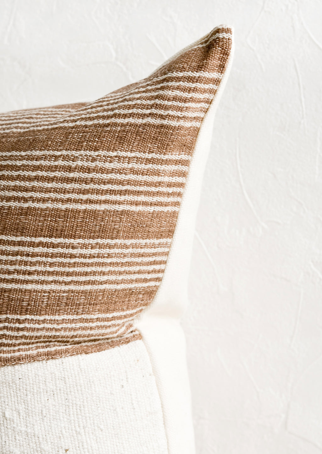 3: A throw pillow with top half in brown & ivory striped fabric and ivory linen back.