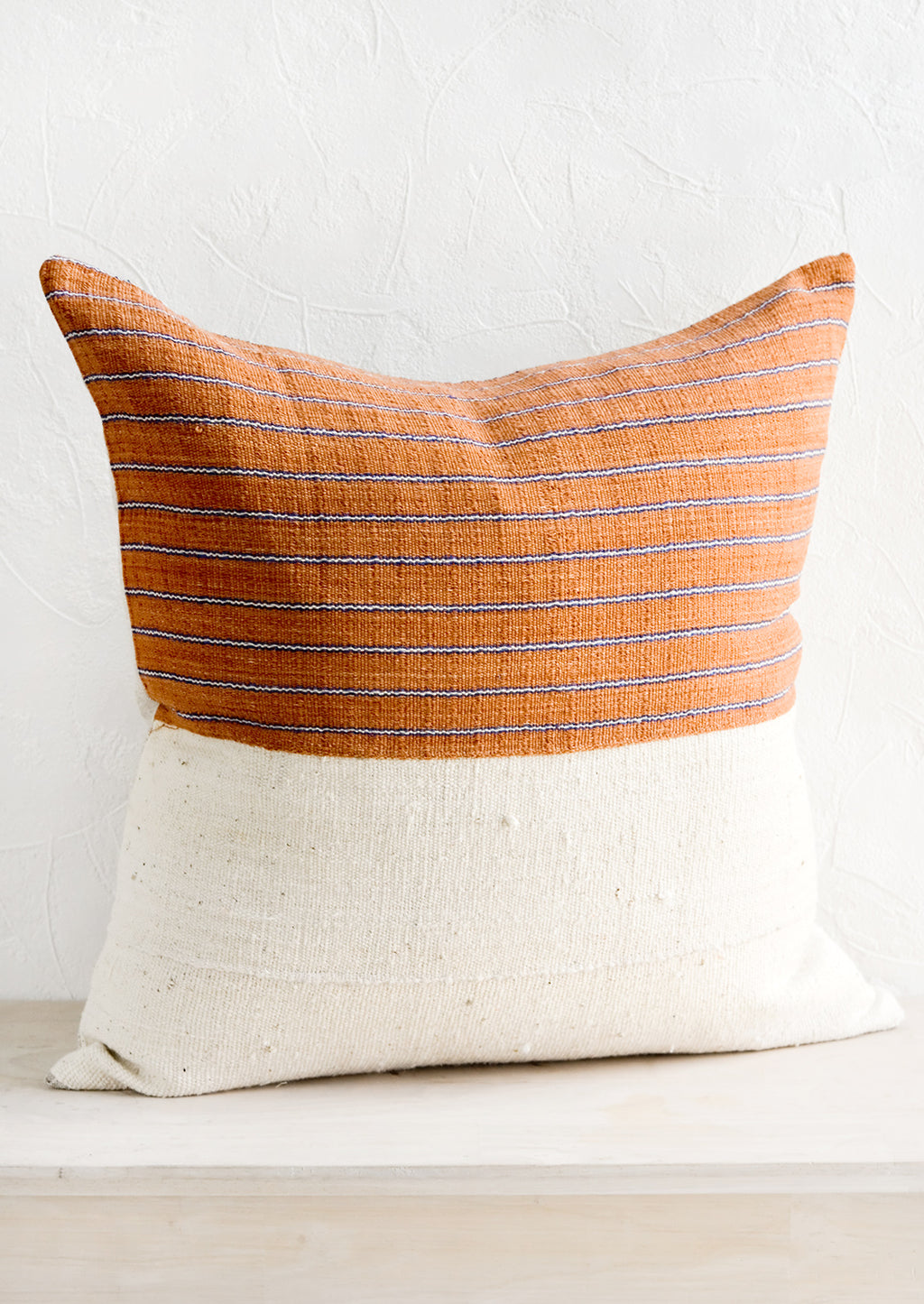 2: A throw pillow with top half in rust & indigo striped fabric and bottom half in natural mudcloth.
