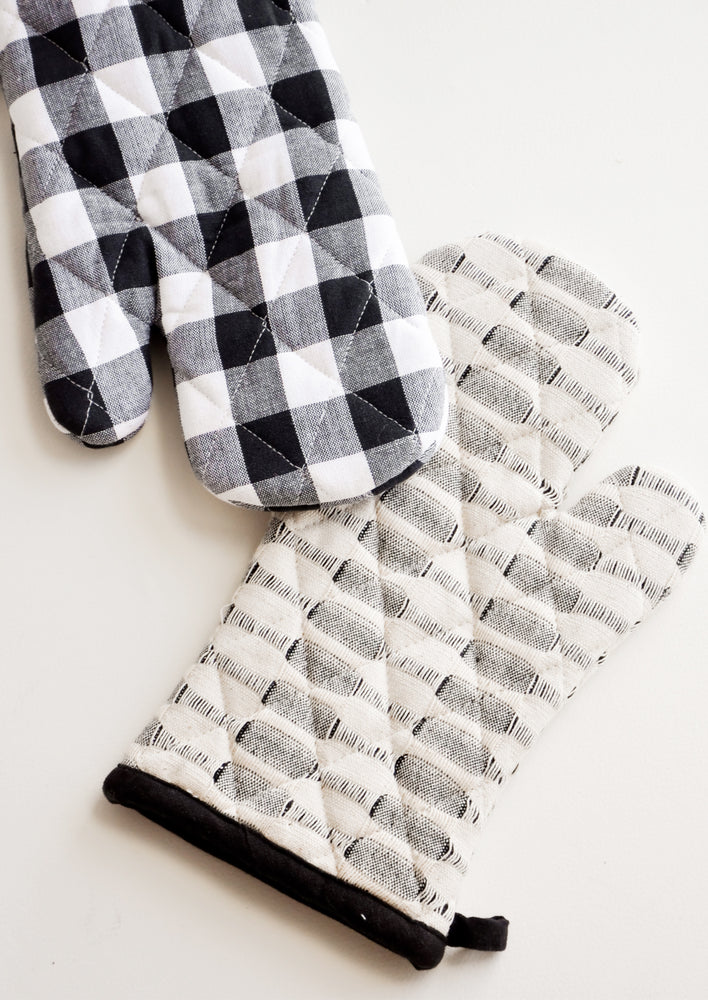 1: Two black and white oven mitts in buffalo check and stipe patterns.