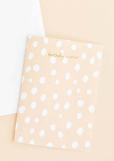 "A white envelope and a peach-hued greeting card with white polka dots and the words ""birthday wishes"" in gold foil at top center."