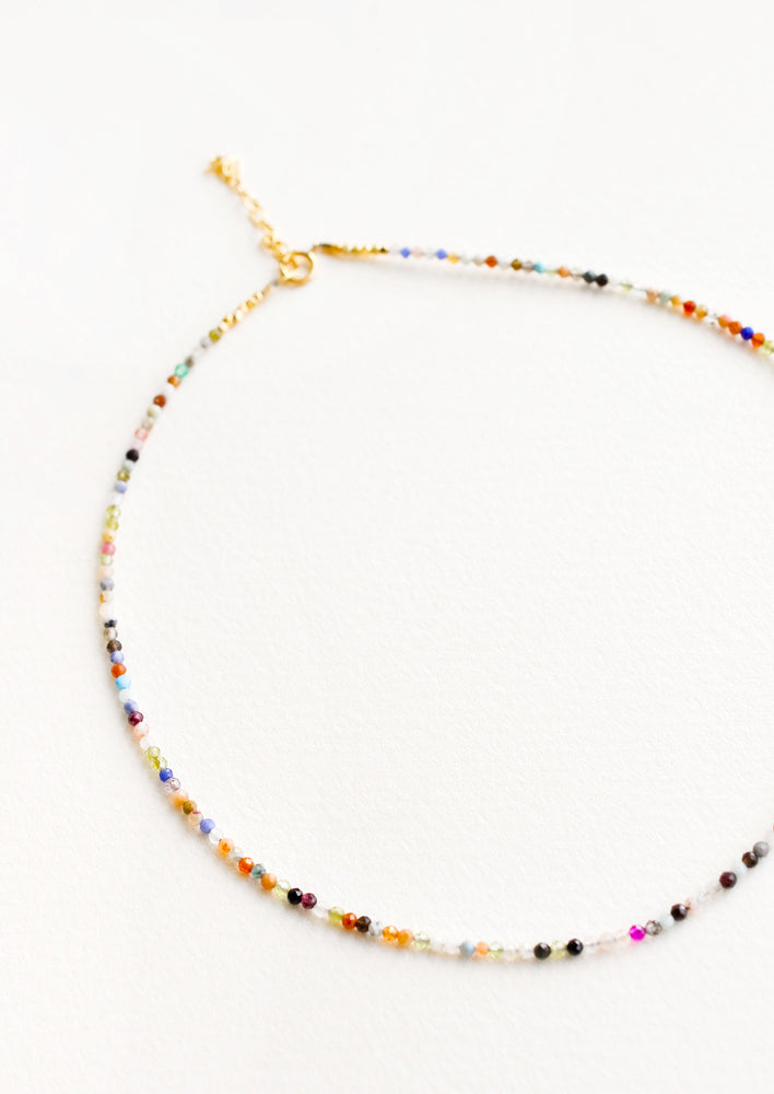 1: Short choker necklace featuring multicolored small gemstones all the way around.
