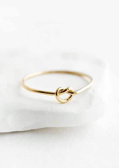A simple gold ring designed for stacking, with single knot detailing at front.
