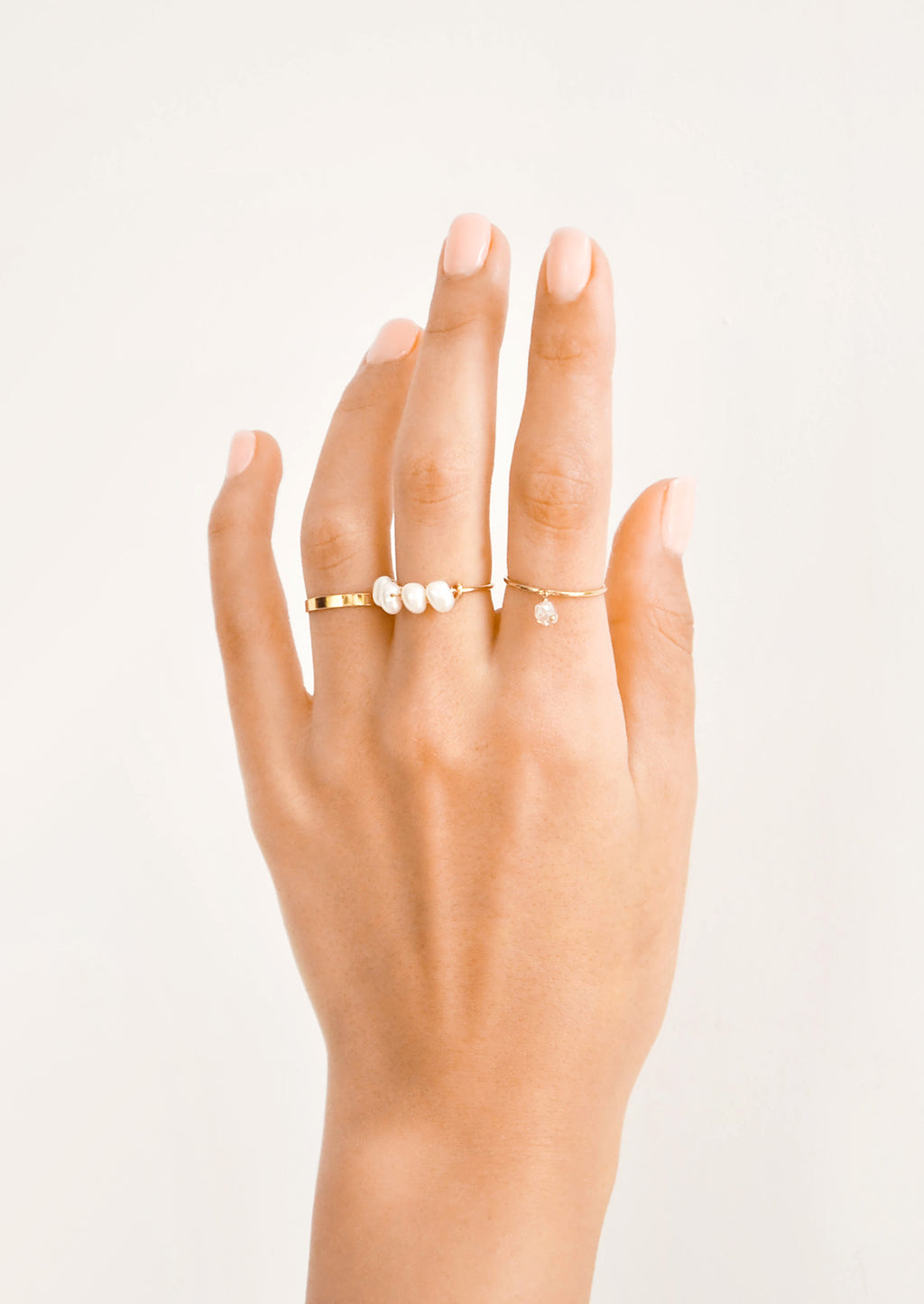 2: Hand modeling assorted gold and pearl rings