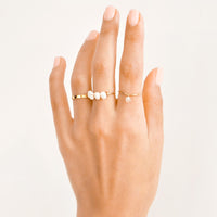 2: Model shot showing hand with several gold rings.