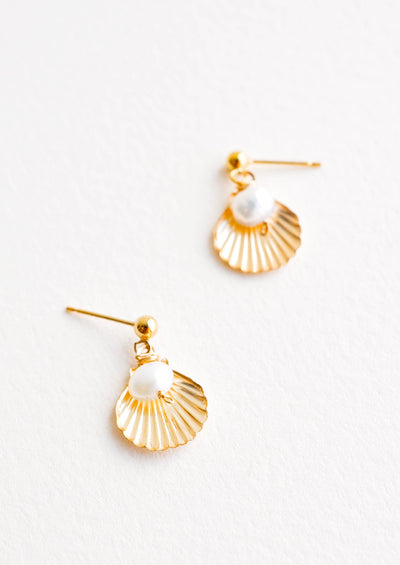 Dangling earring featuring gold shell charm paired with pearl bead, hanging from post.