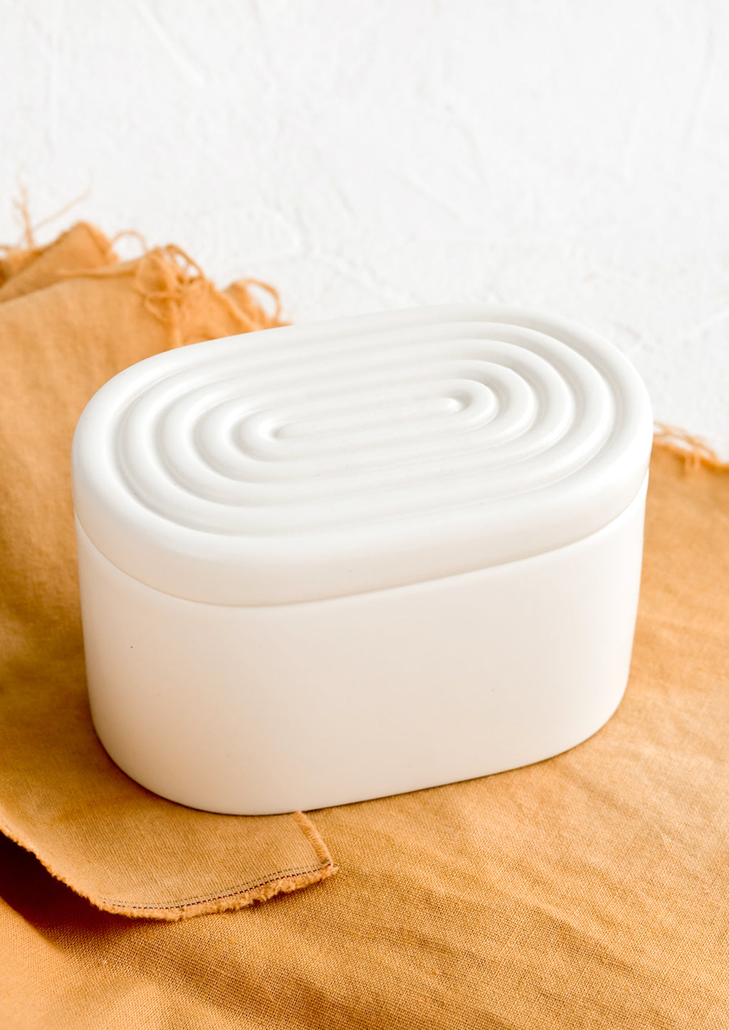 2: An oval-shaped white ceramic storage box with maze-patterned lid.