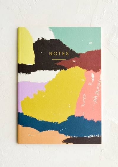 "A notebook with abstract patterned cover and ""NOTES"" in gold letters."