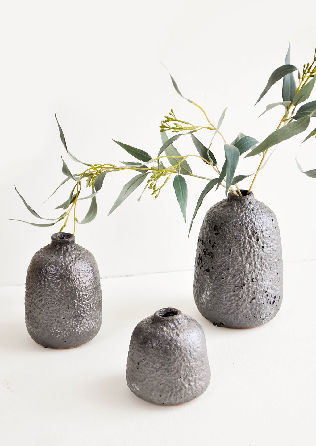 2: Group shot of heavily textured ceramic bud vases in dark metallic grey, styled with eucalyptus stem - LEIF