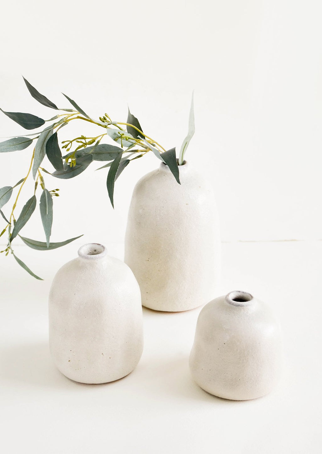 Small / Pumice: Group shot of textured ceramic bud vases in pumice grey, styled with eucalyptus stem