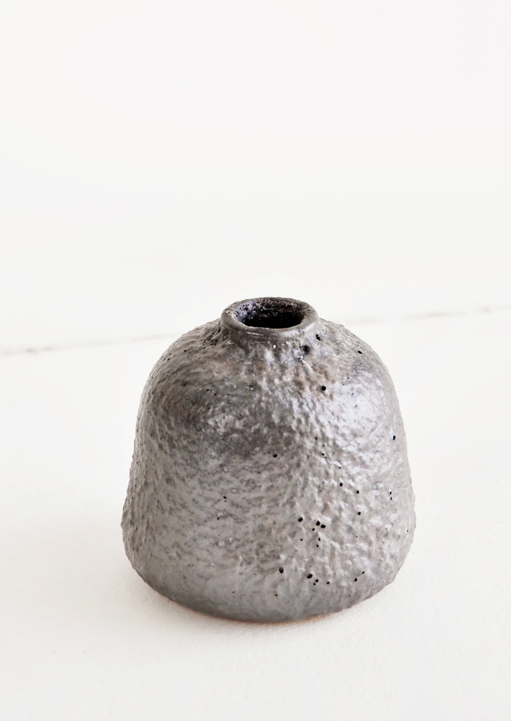 Small / Mercury: Heavily textured, short and wide ceramic bud vase in a metallic, crater-like dark grey glaze