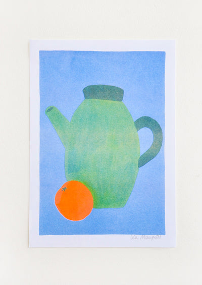 Still life of a green teapot and an orange against a bright blue background.